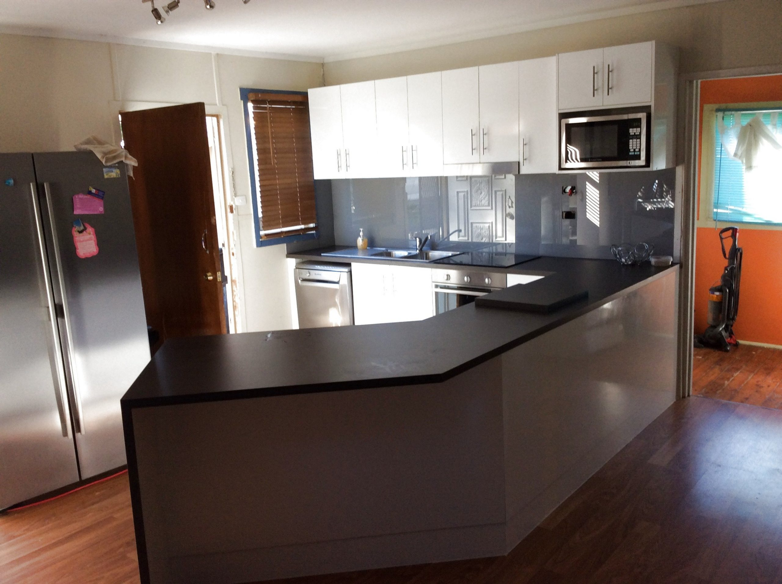 Polytec sheen doors with matte black bench tops and glass splash back